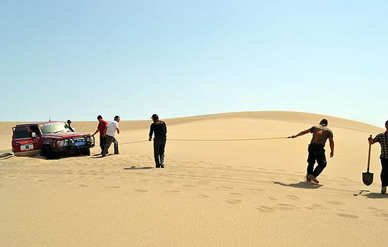 """堪路工作人员在沙漠中解救陷沙车辆   华奥星空讯 至5月初,2013中国环塔(国际)拉力赛的勘路工作已持续半个多月了。勘路所经区域为昌吉、塔城、阿勒泰等北疆地区,现环塔勘路组进入东疆,在哈密周围地区勘测线路,行驶公里数已超过2000公里。在五一期间,国家体育总局汽摩运动管理中心主任韦迪亲赴新疆哈密,特意在五一期间探望在外风餐露宿、辛苦奔波的勘路工作人员。   在哈密期间,韦迪亲自下到赛段中,和勘路人员一起感受和体验勘路的滋味。谈及感受,韦迪表示:""""亲身参与环塔拉力赛的勘路工作这是一种全新的体"""