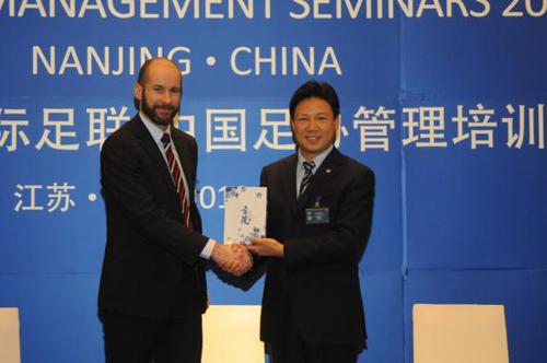 中国足协副主席林晓华向国际足联讲师肯尼斯先生赠送纪念品